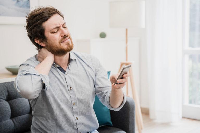 Ser på telefonen med vondt i nakken